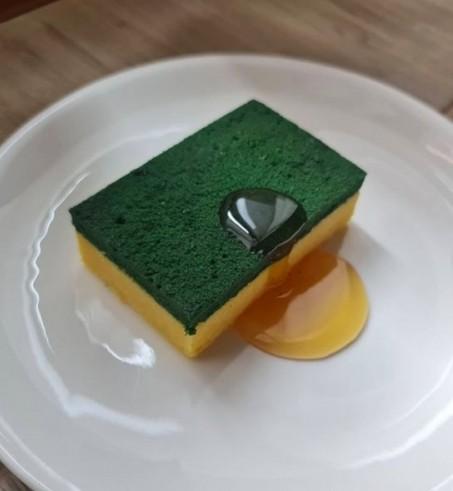 這款蛋糕看起來就彷如人人家裏都有的那塊洗碗百潔布,經典黃和綠的配色,讓人想起上下2種不同的質感,粗糙的綠色刷布和吸水的黃色海綿。蛋糕的表面看起來毛絨絨的,就像用久了稍起毛球的百潔布一樣,相似度十足!